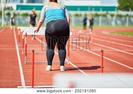 Rear view of overweight female standing by hurdle on stadium
