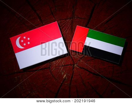 Singaporean Flag With United Arab Emirates Flag On A Tree Stump Isolated