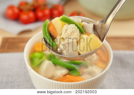 Ladle and bowl with delicious turkey soup on table, closeup