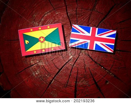 Grenada Flag With British Flag On A Tree Stump Isolated