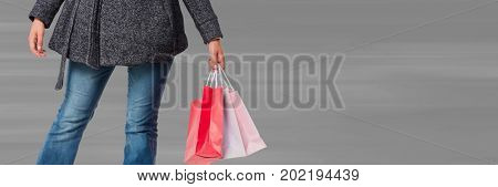 Digital composite of Shopper lower body with bags against blurry grey background