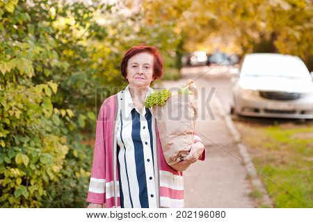 Tired senior woman 70-80 year old holding bag with food walking home outdoors. Looking at camera.