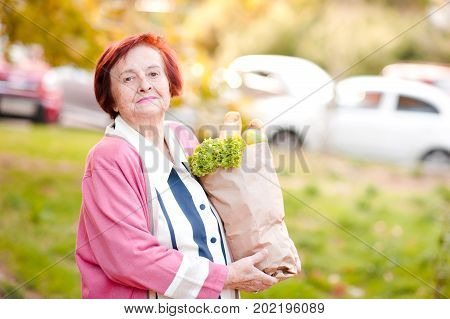 Happy senior woman 70-80 year old holding package with food posing outdoors. Looking at camera. Healthy lifestyle.