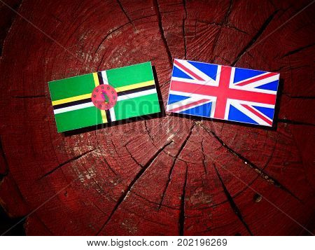 Dominica Flag With British Flag On A Tree Stump Isolated