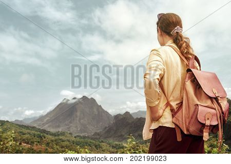 Traveler with backpack enjoying mountains view. Mountains landscape travel alone to Asia happiness emotion summer hike concept.