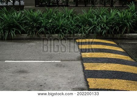 Yellow and gray speed bump on the road for redcing speed.