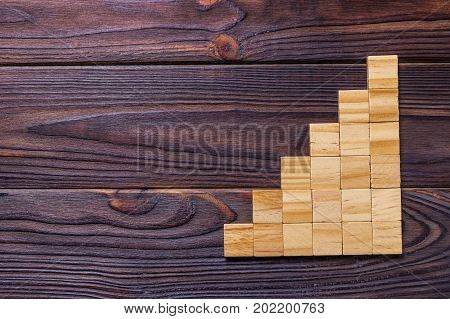 A wooden blocks cube over black wooden textured background with copy space for add word text title. Concept or conceptual Wood block stair or six steps. Cubic.