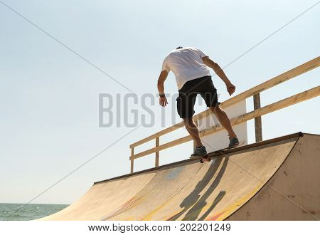 guy skateboarder rides on a ramp on a sunny day.