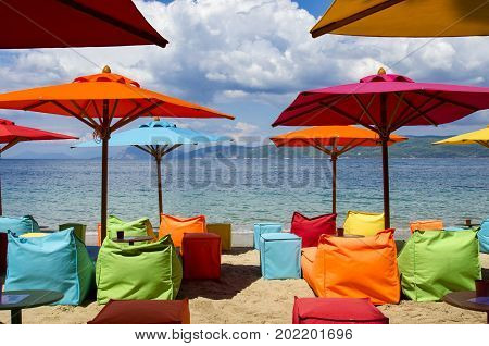 Modern beach equipped with umbrellas and multicolored inflatable deckchairs for trendy tourists Skiathos Greece at the bottom the sea and a cloudy sky