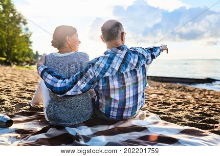 Retired man and woman sitting on sandy beach of summer resort