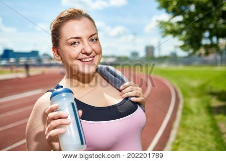 Happy over-sized female with towel and bottle of water