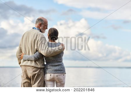 Embracing seniors having talk by seaside during vacation on summer resort