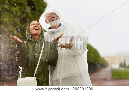 Ecstatic seniors in raincoats having fun in the rain