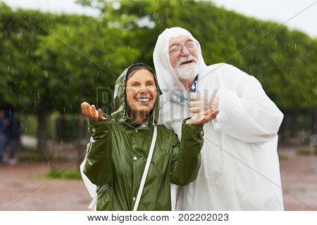 Happy senior couple enjoying rainfall on summer day
