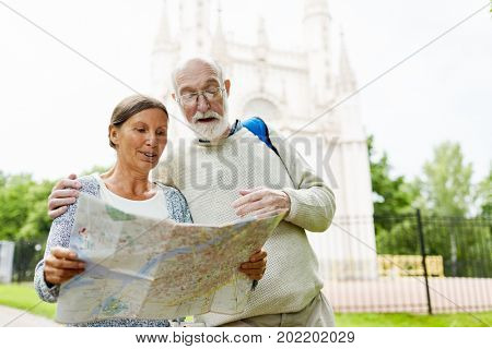 Aged travelers with map looking for places of interest on journey