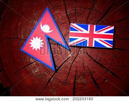 Nepali Flag With British Flag On A Tree Stump Isolated