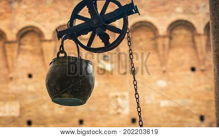Pulley and bucket in a courtyard in Siena Italy
