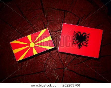 Macedonian Flag With Albanian Flag On A Tree Stump Isolated
