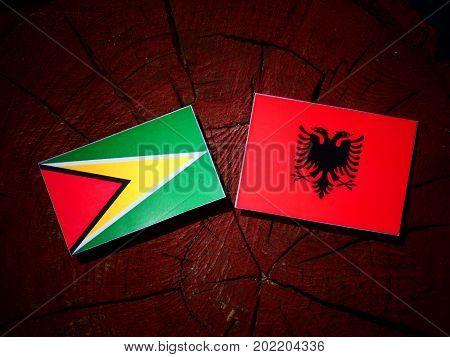 Guyana Flag With Albanian Flag On A Tree Stump Isolated
