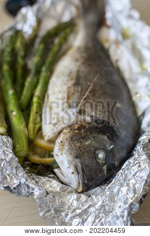 Cooked fish dorada with green asparagus on the foil