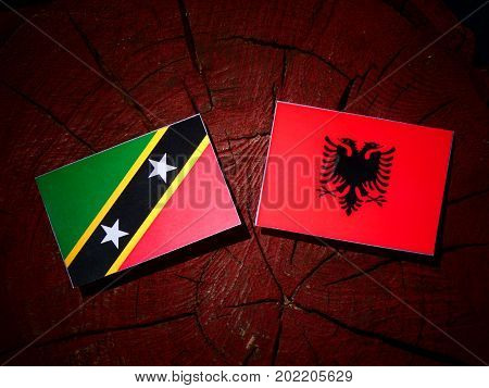 Saint Kitts And Nevis Flag With Albanian Flag On A Tree Stump Isolated
