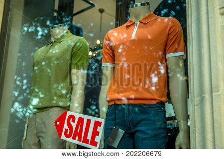 Boutique window with dressed male mannequins and Sale sign arrow on glass