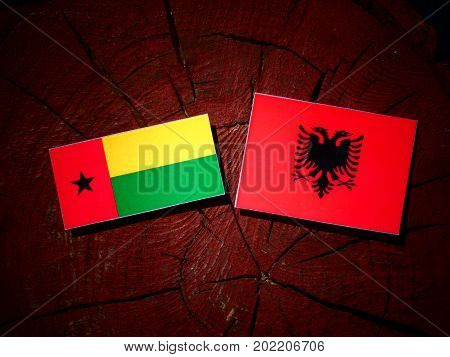 Guinea Bissau Flag With Albanian Flag On A Tree Stump Isolated