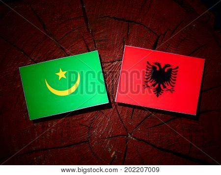 Mauritania Flag With Albanian Flag On A Tree Stump Isolated