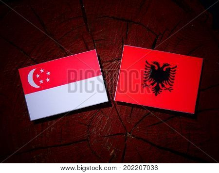 Singaporean Flag With Albanian Flag On A Tree Stump Isolated