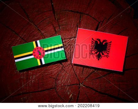 Dominica Flag With Albanian Flag On A Tree Stump Isolated