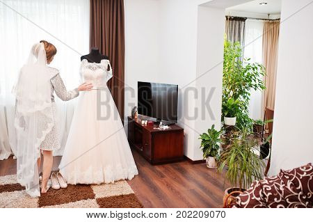 Portrait Of A Bride In Nightgown Posing With Her Wedding Dress In The Room.