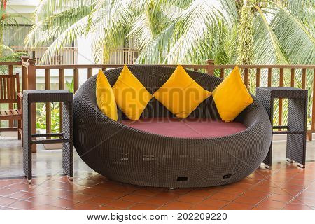 Rattan sofa stick chair furniture in a contemporary style with soft yellow pillows