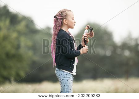 Child girl with pigtails plays with her doll on walk.