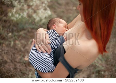 Happy young mother holds newborn baby on her hands and breastfeed on walk.