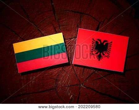 Lithuanian Flag With Albanian Flag On A Tree Stump Isolated