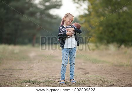 Child girl with her newborn brother on walk in park. Girl holds newborn baby in her hands and looks him with love.