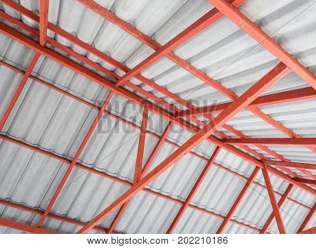 Inside of the Metal roof structure in the warehouse with the white roof tiles.