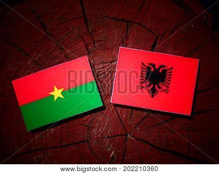 Burkina Faso Flag With Albanian Flag On A Tree Stump Isolated