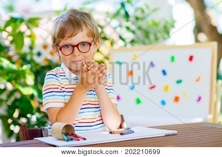 Beautiful adorable little kid boy with glasses holding wax crayons pens. Happy child and student is back to school. Education, school, learning concept. Kid making homework