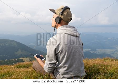 Young male person enjoys music in headset from cell phone in mountains. Man sits top of the hill in carpathian mountains and listens to music in headphones and enjoys beautiful scenery