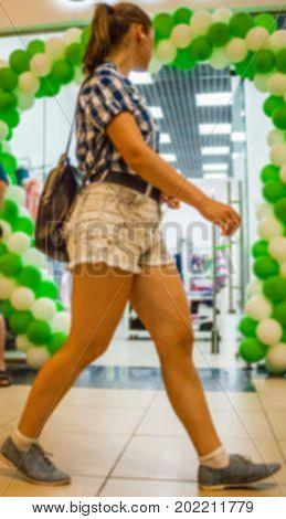Blurred Slender Girl In Short Shorts Walking On The Shopping Center