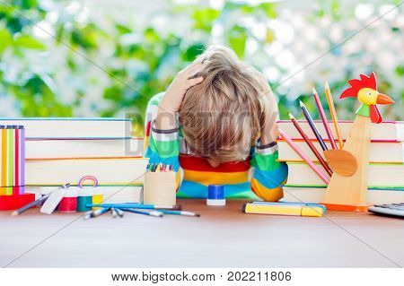 Frustrated sad little kid boy with glasses and lots of pupil's stuff like crayons pencils, scissors and books. Tired child and student is back to school and unhappy about begin of lessons.