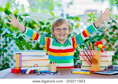 Adorable beautiful little kid boy with glasses and lots of pupil's stuff like crayons pens, scissors and books. Child and student is back to school and happy about begin of lessons.