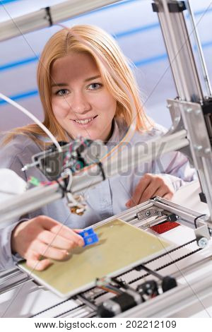 A female student or laboratory assistant in the automation laboratory is debugging the work of the 3d printer. 3d printer is a device for modeling 3D objects