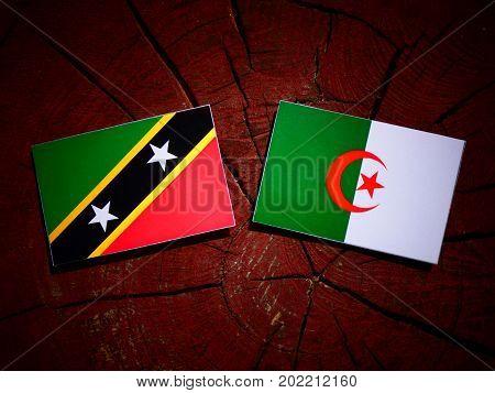 Saint Kitts And Nevis Flag With Algerian Flag On A Tree Stump Isolated