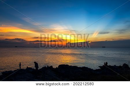Silhoutte people standing ledge of a mountain enjoying the beautiful sunset and twilight over a wide sea in Thailand