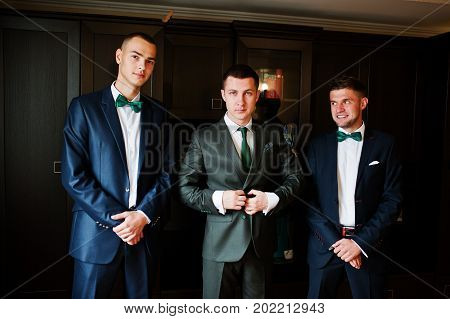 Handsome Groom Posing With His Groomsmen In The Room Before A Wedding.