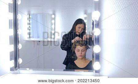 Professional hairdresser, stylist combing hair of female client and using barrette for fixing hairdo in white make up room. Beauty and haircare concept
