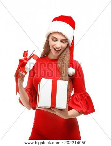 Beautiful young woman in Santa hat opening giftbox, on white background