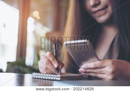 Closeup image of a business woman writing on notebook while using and holding mobile phone on wooden table background in office